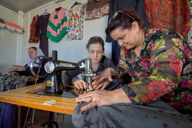 """Janet da clases de costura a mujeres yazidíes en un """"espacio de acogida para las mujeres"""" en un campo para personas desplazadas internas en Dawodiya, en la región del Kurdistán Iraquí. Fotografía: Paul Jeffrey/ACT Alianza."""